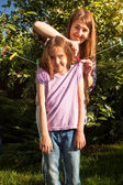 woman hanging girl on clothesline at garden — ストック写真
