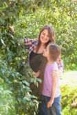 Smiling mother and daughter posing at apple garden at sunny day — Stock Photo