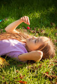 Little girl lying on grass and looking at red cherry — Stock Photo