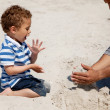 Royalty-Free Stock Photo: Kid Looking as His Dad Makes Sand Castle