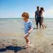 Young Couple Watches as Son Walks Away from the Water — Stock Photo