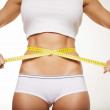 Stock Photo: Fit woman in underwear with measure tape