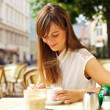 Smiling Woman Having Coffee at a Cafe — Stock Photo #16904953