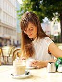 улыбается женщина, выпить кофе в кафе — Стоковое фото