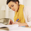 Foto Stock: Indoor Woman Studying at Home Writing Something