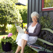 Elder woman reading newspaper in backyard garden — Stock Photo