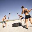 Постер, плакат: Athletes doing crossfit workout on beach