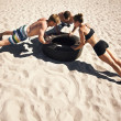 Young athletes doing push-ups on tire — Stock Photo
