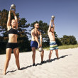 Group of athletes working out with kettle bell on beach — Stock Photo