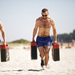 Foto Stock: Crossfit Men Lifting Heavy Jerrycans
