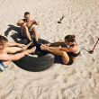 Group of athletes doing crossfit exercise routine on beach — Stock Photo #31149785