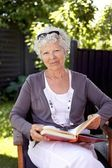 Happy mature woman with novel in garden — Stock Photo
