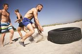 Tire flip crossfit exercise on beach — Stock Photo
