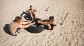 Group of athletes doing crossfit exercise routine on beach — Stock Photo