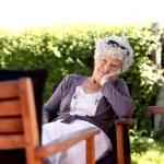 Senior woman relaxing in backyard garden — Stock Photo