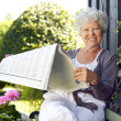 Senior woman reading newspaper in backyard garden — Stock Photo