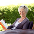 Happy senior woman reading book in the garden — Stock Photo