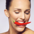 Young beauty biting red chili pepper — Stock Photo