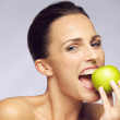 Young happy woman eating green apple — Stock Photo