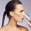 Young beautiful woman drinking a glass of mineral water — Stock Photo