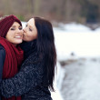Attractive female kissing her friend on the cheek — Stock Photo