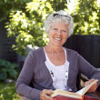 Elderly woman with novel in garden — Foto Stock