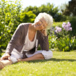 Happy senior woman sitting relaxed in garden — Stock Photo
