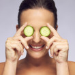 Woman holding slices of cucumber over eyes — Stock Photo