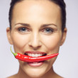 Beauty with hot pepper in her mouth — Stock Photo