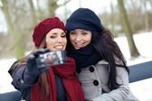 Two Beautiful Women with Camera Phone in a Park — Stock Photo