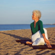 Senior woman performing a yoga routine on the beach — Stok fotoğraf