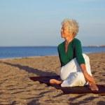 Senior woman performing a yoga routine on the beach — Stock Photo