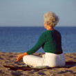 Senior woman doing yoga meditation on beach — Stock Photo