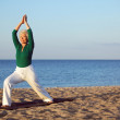 Mature woman stretching on the beach — Stock Photo
