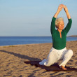 Senior woman stretching on the beach — Stock Photo