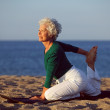 Senior woman doing yoga by the ocean — Stock Photo