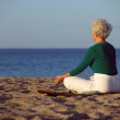Elder woman doing yoga meditation on beach — Stock Photo