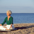 Senior caucasian woman meditating on the beach — Stock Photo