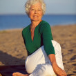 Senior woman enjoying yoga on the beach — Stock Photo