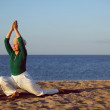 Senior woman practicing yoga on beach — Stock Photo