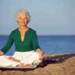 Senior woman meditating on sandy beach — Stock Photo
