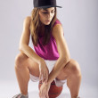Attractive young female basketball player sitting on ball — Stock Photo