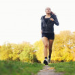 Healthy young woman jogging in park — Stock Photo