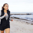 Fit and healthy woman jogging on beach — Stock Photo