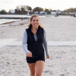 Young female athlete walking on beach smiling — Stock Photo