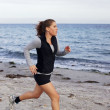 Foto Stock: Female runner running on seashore