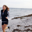 Stock Photo: Fit young womjogging on seshore