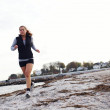 Stock Photo: Young womjogging along beach