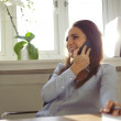 Pretty woman talking on mobile phone in home office — Stock Photo