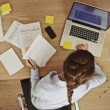 Businesswoman working at her office desk with documents and laptop — ストック写真